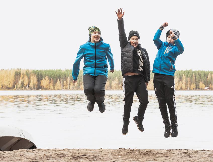 3 poikaa hyppää järven rannalla syksyllä
