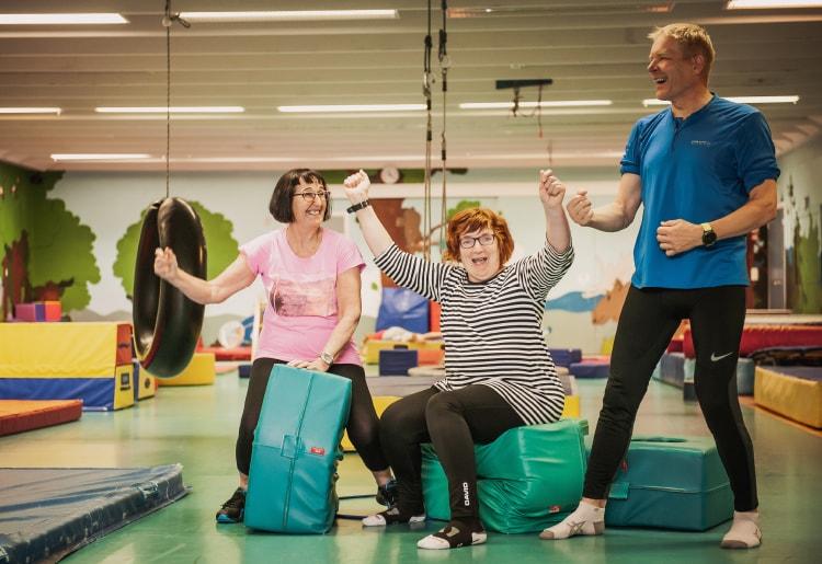 Kaksi naista ja mies tuulettavat iloisesti liikuntasalissa.