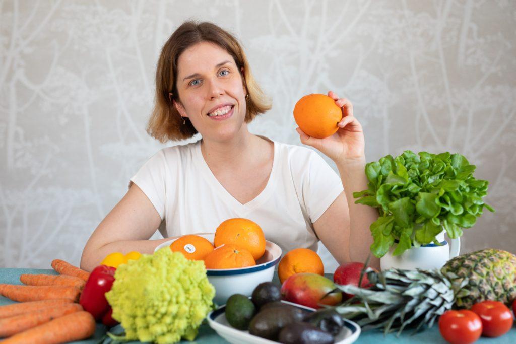 Hymyilevä nainen istuu hedelmiä ja kasviksia täynnä olevan pöydän ääressä ja pitää appelsiinia kädessään.