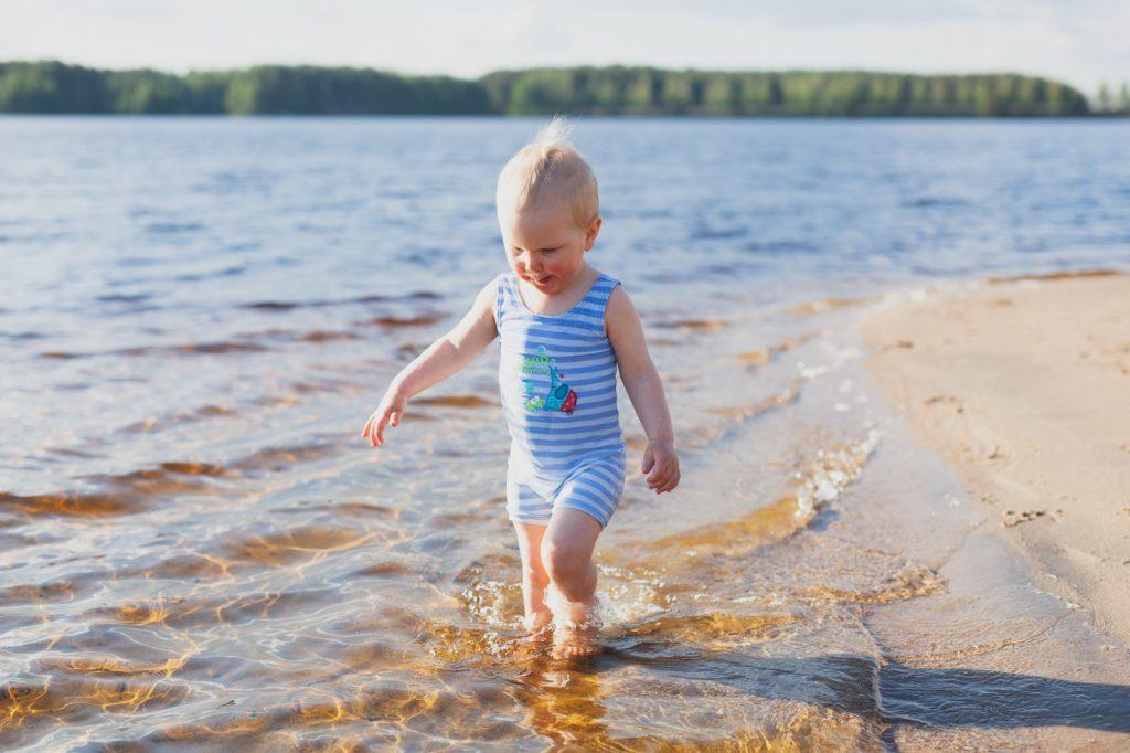 Taapero kävelee rannalla uimapuvussa.