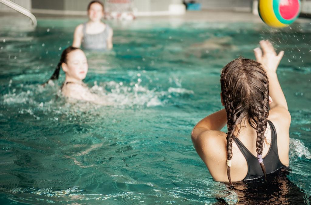Tyttö heittää palloa uimahallin altaassa.