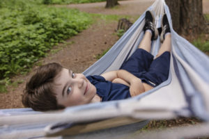 Poika makaa riippumatossa ja katsoo kameraan.