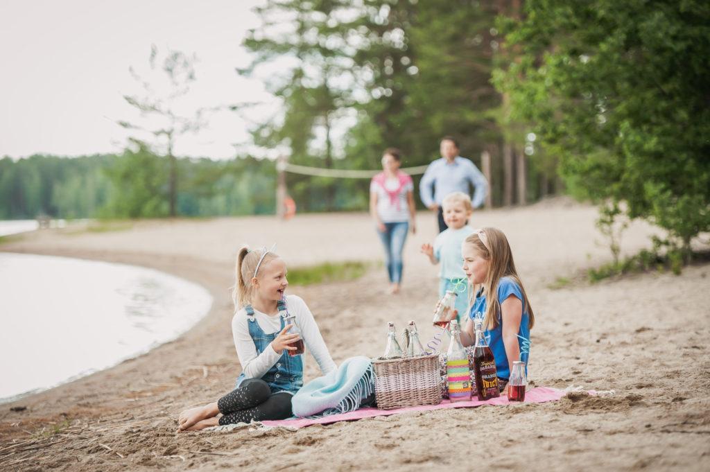 Tytöt istuvat Piispalan rannalla viltin päällä