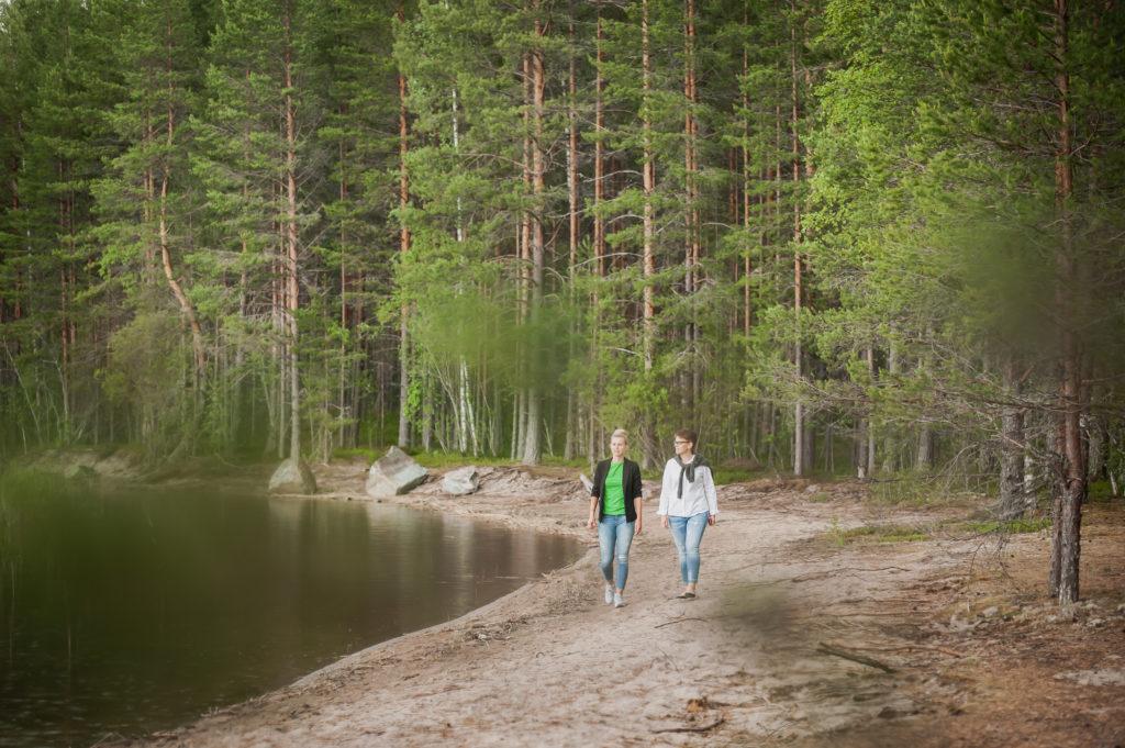 Kaksi naista kävelee hiekkarannalla ja katselee järvelle.