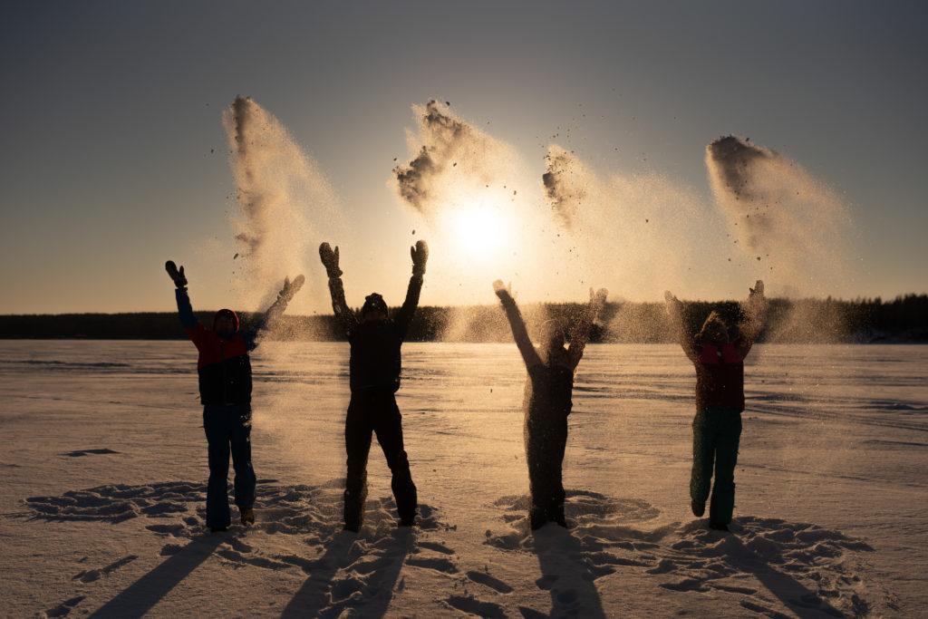 Neljä nuorta seisoo jäällä ja heittää lunta ilmaan.
