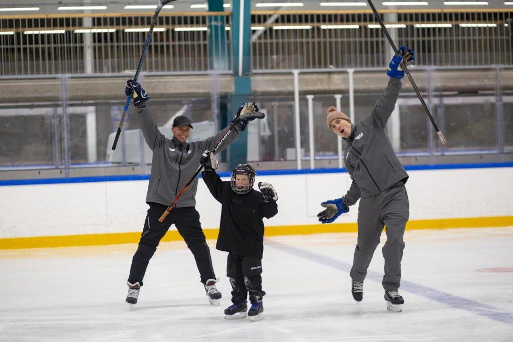 Kaksi miestä ja poika tuulettavat jääkiekkokaukalossa.