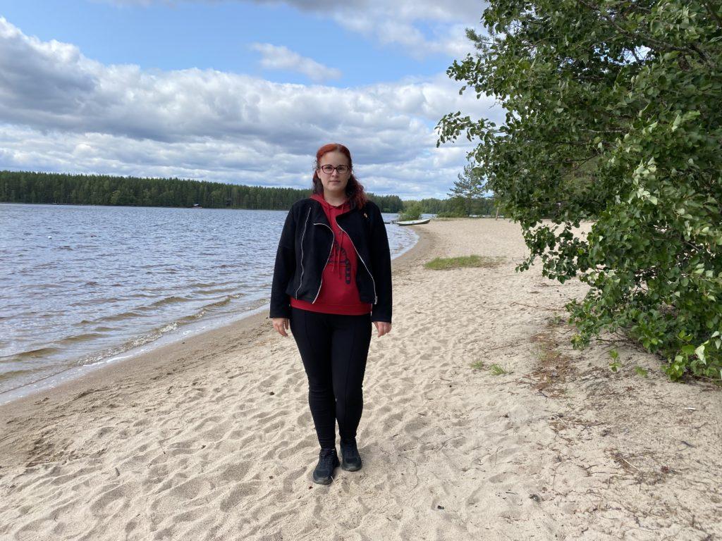Nainen seisoo rannalla puun vieressä lähellä vedenrajaa
