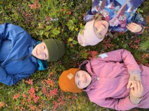 Kolme lasta makaa sammaleella metsässä.