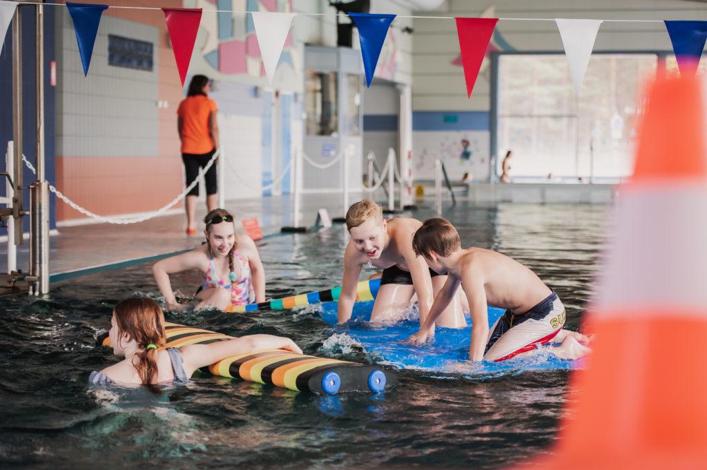 Lapsia uima-altaassa vesiseikkailu-leirikouluohjelmassa.