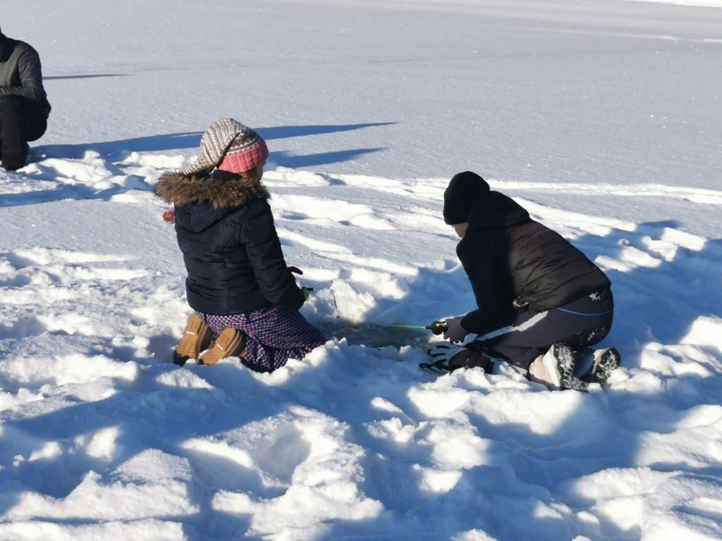 Kaksi leirikouluoppilasta pilkkii jäällä.